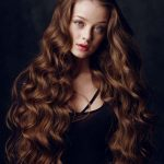 Beautiful redhead with evening make-up and long shiny wavy hair
